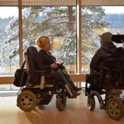 Two wheelchair users looking out into a snowy forest